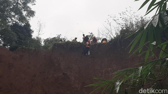 Petugas evakuasi jenaah di bibir tebing yang longsor