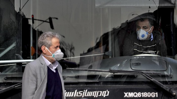 A public bus driver, right, and a pedestrian wear masks to help guard against the Coronavirus in downtown Tehran, Iran, Sunday, Feb. 23, 2020. On Sunday Irans health ministry raised the death toll from the new virus to 8 people in the country, amid concerns that clusters there, as well as in Italy and South Korea, could signal a serious new stage in its global spread. (AP Photo/Ebrahim Noroozi)