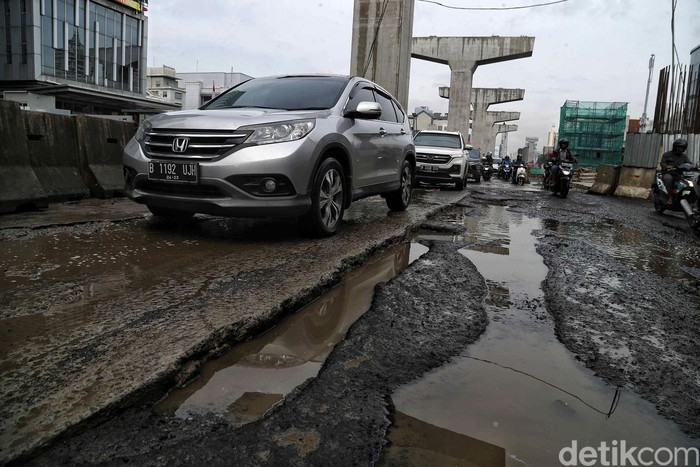 Sejumlah kendaraan melintas di Jalan Boulevard Raya yang rusak kawasan Kelapa Gading, Jakarta Utara, Jumat (28/2). Menurut keterangan warga jalan tersebut rusak karena proyek jalan tol dan akibat dampak banjir yang memperparah kerusakan sehingga jalanan menjadi penuh lubang dan becek menyebabkan bahaya kepada pengendara motor.