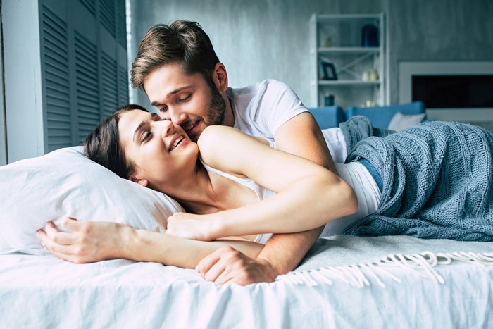 Young loving couple enjoying in their morning time and talking to each other in bedroom.