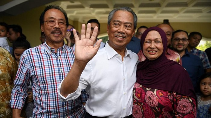 Malaysias former interior minister Muhyiddin Yassin (C), his wife Noraini Abdul Rahman  talk to the press outside his home in Kuala Lumpur on February 29, 2020. - Muhyiddin was named as Malaysias new prime minister on February 29, royal officials said, signalling the end of Mahathir Mohamads rule and return to power of a scandal-plagued party. (Photo by Mohd RASFAN / AFP) / The erroneous mention[s] appearing in the metadata of this photo by Mohd RASFAN has been modified in AFP systems in the following manner: [---] instead of [Malaysian politician Anwar Ibrahim (L)]. Please immediately remove the erroneous mention[s] from all your online services and delete it (them) from your servers. If you have been authorized by AFP to distribute it (them) to third parties, please ensure that the same actions are carried out by them. Failure to promptly comply with these instructions will entail liability on your part for any continued or post notification usage. Therefore we thank you very much for all your attention and prompt action. We are sorry for the inconvenience this notification may cause and remain at your disposal for any further information you may require.