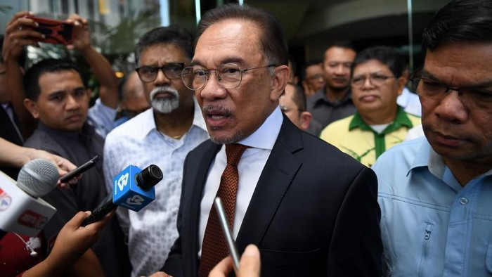 Malaysian politician Anwar Ibrahim (C) speaks to journalists outside a hotel in Kuala Lumpur on February 29, 2020, before departing to the National Palace for an audience with Malaysias King Sultan Abdullah Sultan Ahmad Shah. (Photo by Mohd RASFAN / AFP)