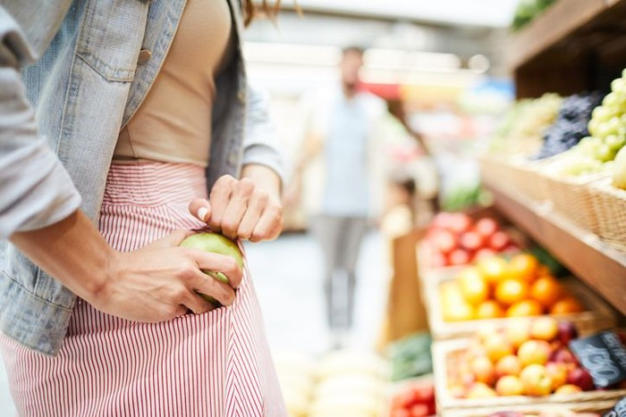 Close-up of unrecognizable woman in stripped skirt hiding apple in pocket while stealing it in food store