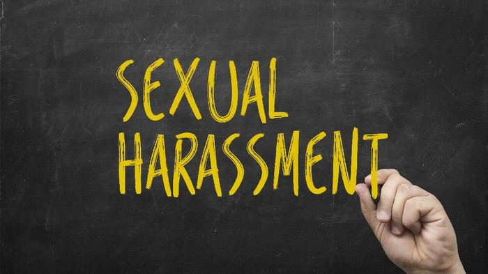 hand writing sexual harassment on blackboard. Symbol of violence against women