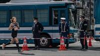 Seorang pelari yang ikut serta dalam Maraton Tokyo 2020 melintas di samping sejumlah petugas kepolisian yang bertugas di area sekitar kegiatan olahraga internasional tersebut.