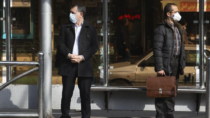 Men wearing face masks wait for a bus in northern Tehran, Iran, Sunday, March 1, 2020. While the new coronavirus has extended its reach across the world, geographic clusters of infections were emerging, with Iran, Italy and South Korea seeing rising cases. (AP Photo/Vahid Salemi)