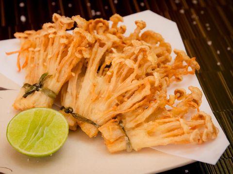 deep fried golden brown crispy Japanese enokitake needle shape mushroom with lime on black background