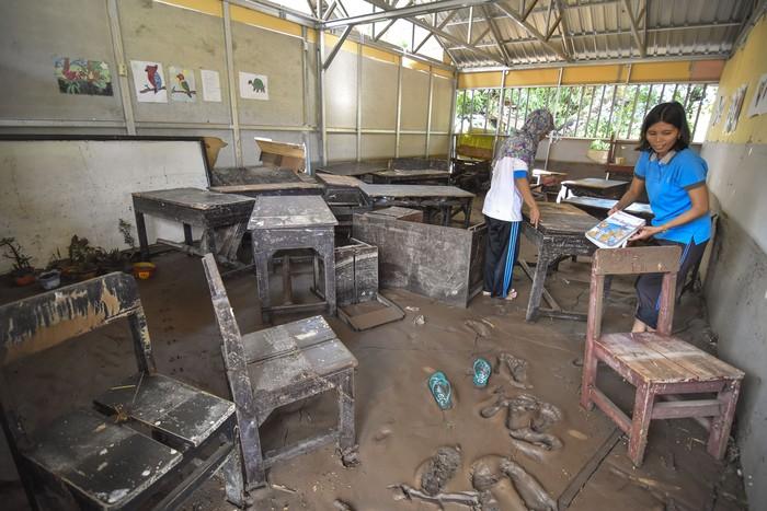 Sejumlah guru mengangkat kursi dari ruang kelas yang terdampak banjir di SMPN 2 Gunungsari, Desa Mekarsari, Kecamatan Gunungsari, Lombok Barat, NTB, Senin (2/3/2020). Banjir yang terjadi karena hujan lebat dan luapan air sungai pada Minggu (1/3/2020) pukul 18.00 WITA di wilayah tersebut mengakibatkan lima ruang kelas rusak ringan dan sebanyak 155 siswa diliburkan. ANTARA FOTO/Ahmad Subaidi/foc.