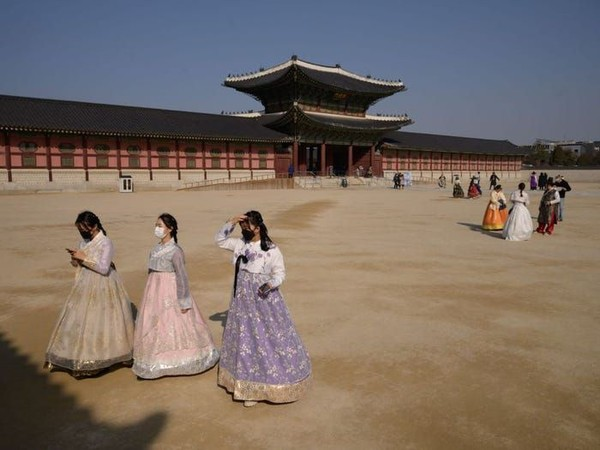 Korea Selatan juga menjadi negara yang terdampak virus Corona. Meski demikian, masih ada turis yang datang ke Gyeongbokung Palace dengan menggunakan masker. (ED JONES/AFP via Getty Images)