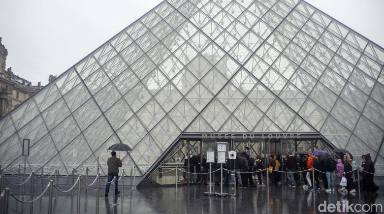 People walk by the Louvre museum, in Paris, France, Sunday, March 1, 2020. The spreading coronavirus epidemic shut down Frances Louvre Museum on Sunday, with workers who guard its trove of artworks fearful of being contaminated by the museums flow of visitors from around the world. (AP Photo/Rafael Yaghobzadeh)