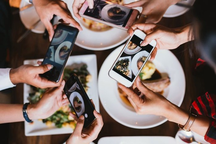 Close up focus view of hand and mobile while taking a photo of food on the plate in a restaurant for social media.