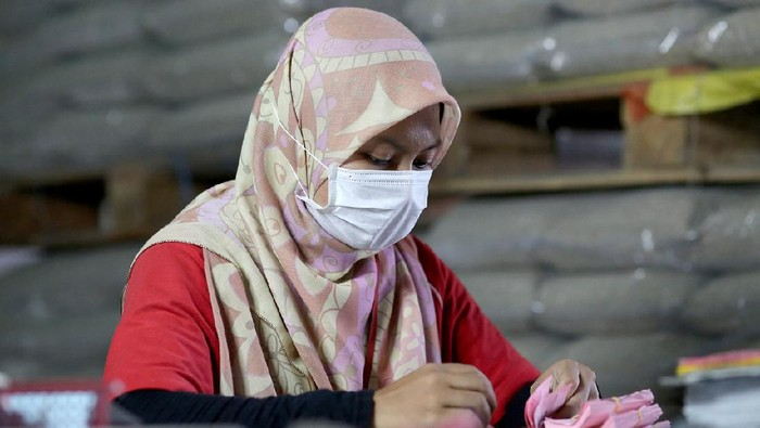 A Muslim female adult is working on documentation and labelling department in paddy factory.