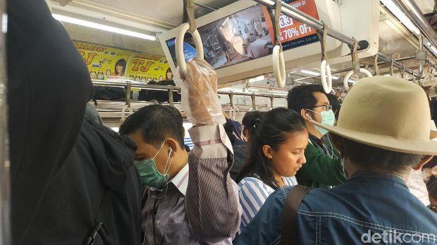 Penumpang KRL Commuter Line menggunakan sarung tangan plastik untuk cegah virus corona.