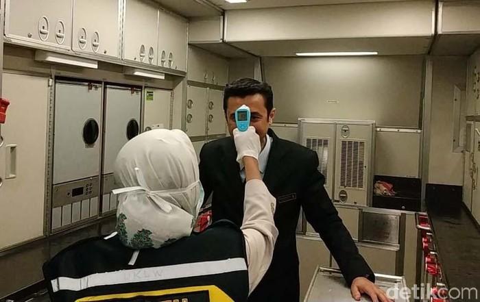 Puluhan penumpang yang datang dari Singapura dan Malaysia mendapat pemeriksaan thermo gun. Pemeriksaan dilakukan di Bandara International Juanda Surabaya.