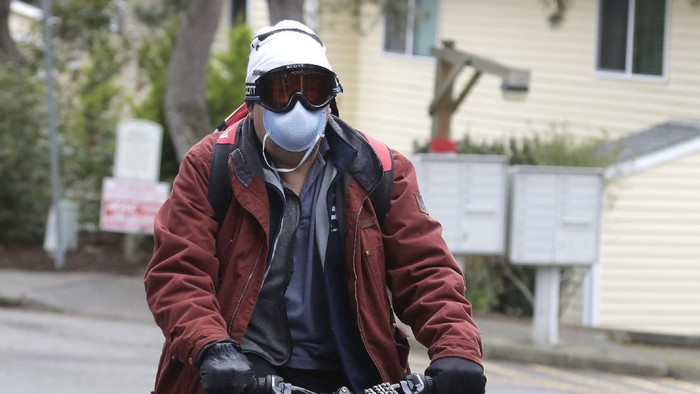 A man wearing a mask and goggles rides his bike out of the parking lot at the Life Care Center is shown in Kirkland, Wash., near Seattle, Tuesday, March 3, 2020. The facility has been tied to several confirmed cases of the COVID-19 coronavirus. (AP Photo/Ted S. Warren)