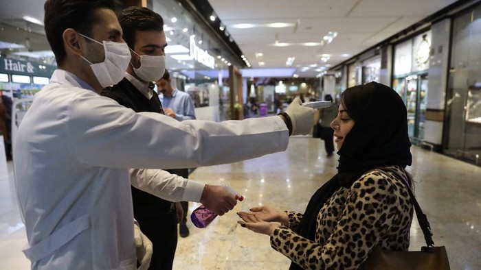 A woman has her temperature checked and her hands disinfected as she enters the Palladium Shopping Center, in northern Tehran, Iran, Tuesday, March 3, 2020. Irans supreme leader put the Islamic Republics armed forces on alert Tuesday to assist health officials in combating the outbreak of the new coronavirus, the deadliest outside of China. (AP Photo/Vahid Salemi)