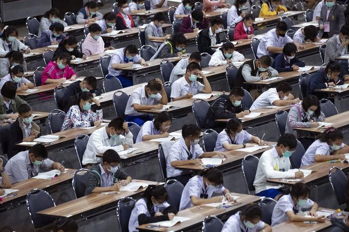 Siswa di Thailand ramai-ramai mengenakan masker saat mengikuti ujian masuk sekolah menengah. Hal itu dilakukan guna mencegah penyebaran virus corona.