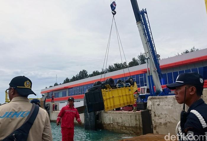 Truk muatan semen nyemplung ke laut di Pelabuhan Merak, Banten. Proses evakuasi dengan menggunakan crane dilakukan untuk mengangkat truk itu ke dermaga.