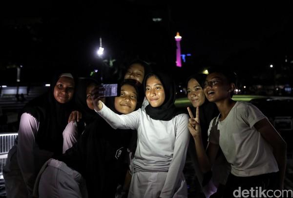 Tak sedikit warga yang berfoto bersama dengan latar warna-warni lampu yang menghiasi ibu kota di kawasan Lapangan Banteng.