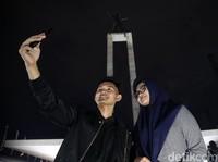 Dua orang pengunjung tampak asyik berfoto di kawasan Lapangan Banteng, Jakarta, di kala malam, Rabu (4/3/2020).