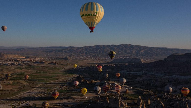 NEVSEHIR, TURKEY - APRIL 17:  Tourists ride hot air balloon near the town of Goreme on April 17, 2016 in Nevsehir, Turkey. Cappadocia, a historical region in Central Anatolia dating back to 3000 B.C is one of the most famous tourist sites in Turkey. Listed as a World Heritage Site in 1985, and known for its unique volcanic landscape, fairy chimneys, large network of underground dwellings and some of the best hot air ballooning in the world, Cappadocia is preparing for peak tourist season to begin in the first week of May.  Despite Turkeys tourism downturn, due to the recent terrorist attacks,  internal instability and tension with Russia, local vendors expect tourist numbers to be stable mainly due to the unique activities on offer and unlike other tourist areas in Turkey such as Antalya, which is popular with Russian tourists, Cappadocia caters to the huge Asian tourist market.  (Photo by Chris McGrath/Getty Images)