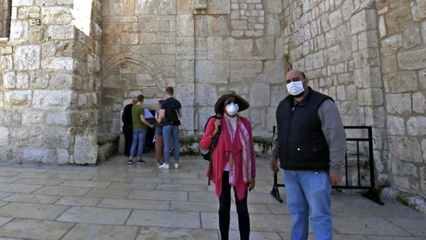 People wearing masks visit the Church of the Nativity, revered as the birthplace of Jesus Christ, in the West Bank city of Bethlehem on March 5, 2020. - The Palestinian health ministry called for local churches, mosques and other institutions to close after suspected cases had been detected at the hotel in the Bethlehem area, the first in the Palestinian territories. (Photo by Musa Al SHAER / AFP)