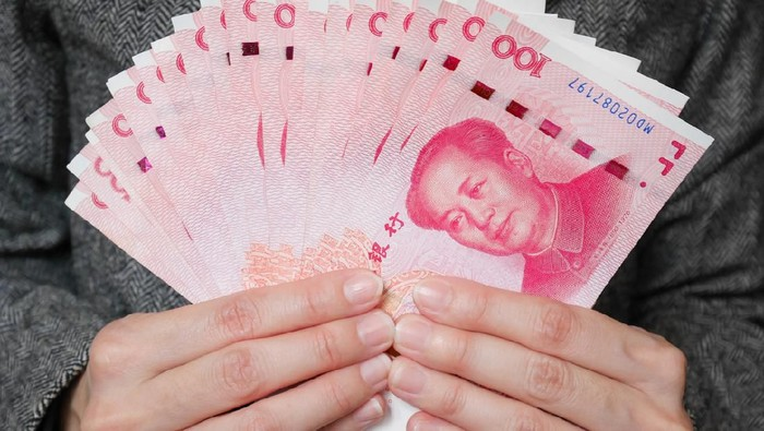 Business woman holding stack of 100 yuan banknotes money. Chinese yuan currency