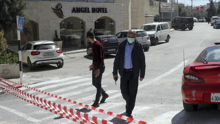 Palestinian policeman stands outside a hotel in Bethlehem, West Bank, Thursday, March 5, 2020 where some of the hotel staff was tested positive to coronovirus. The Palestinian Health Ministry said it was preventing all tourists from entering the West Bank, where Bethlehem is located. (AP Photo/Mahmoud Illean)