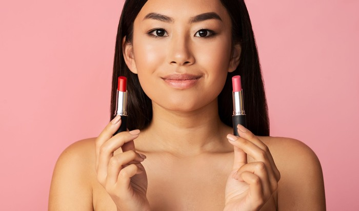 Makeup concept. Asian girl holding two lipsticks over pink studio background, panorama