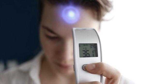 Alat thermal gun untuk mengukur suhu tubuh.