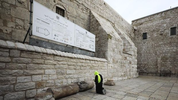 A pilgrim prays outside the Church of the Nativity in Bethlehem, West Bank, Thursday, March 5, 2020. Palestinian authorities said the Church of the Nativity in Bethlehem, built atop the spot where Christians believe Jesus was born, will close indefinitely due to coronavirus concerns. (AP Photo/Mahmoud Illean)