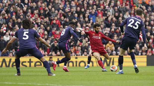 Liverpool's Mohamed Salah, second from right, scores his side's opening goal during the English Premier League soccer match between Liverpool and Bournemouth at Anfield stadium in Liverpool, England, Saturday, March 7, 2020. (AP Photo/Jon Super)