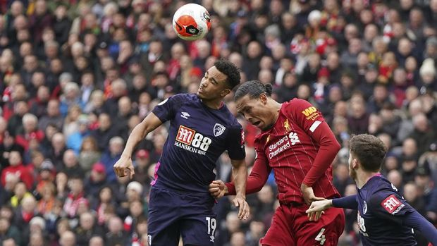 Bournemouth's Junior Stanislas, left, jumps for the ball with Liverpool's Virgil van Dijk, center, during the English Premier League soccer match between Liverpool and Bournemouth at Anfield stadium in Liverpool, England, Saturday, March 7, 2020. (AP Photo/Jon Super)