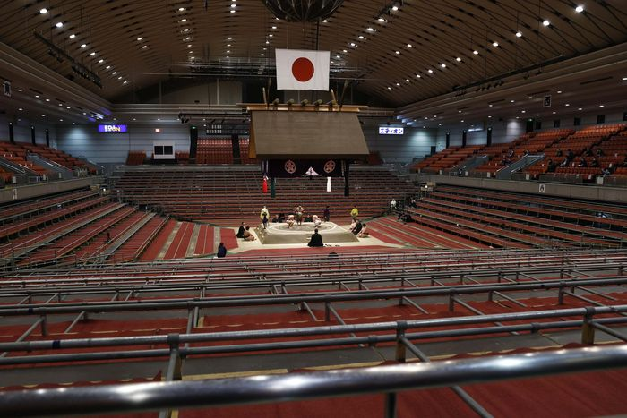 Sumo wrestlers fight on the ring as spectators seats are empty during the Spring Grand Sumo Tournament in Osaka, western Japan, Sunday, March 8, 2020. The 15-day sumo tournament started on Sunday with no spectators, affected by fears of the new coronavirus outbreak. (Kyodo News via AP)