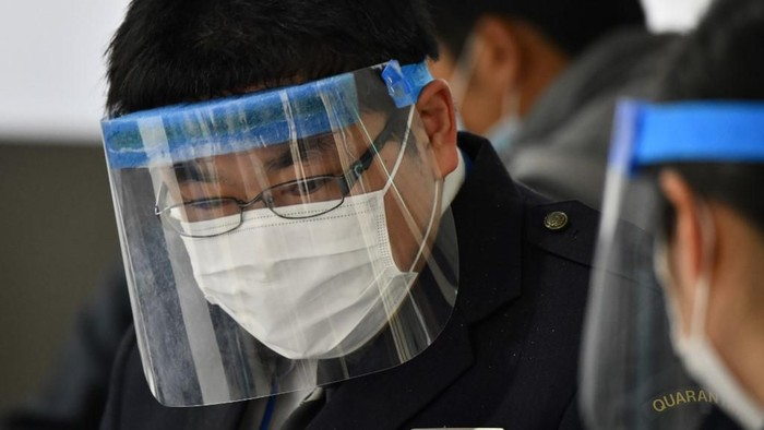 An officer wearing a face mask and shield works at a quarantine station at Narita airport, Chiba prefecture on March 9, 2020. - Japanese Prime Minister Shinzo Abe on March 5 announced that foreign arrivals who have recently been in China or South Korea would be required to spend 14 days in quarantine amid concerns of the COVID-19 novel coronavirus. (Photo by Kazuhiro NOGI / AFP)