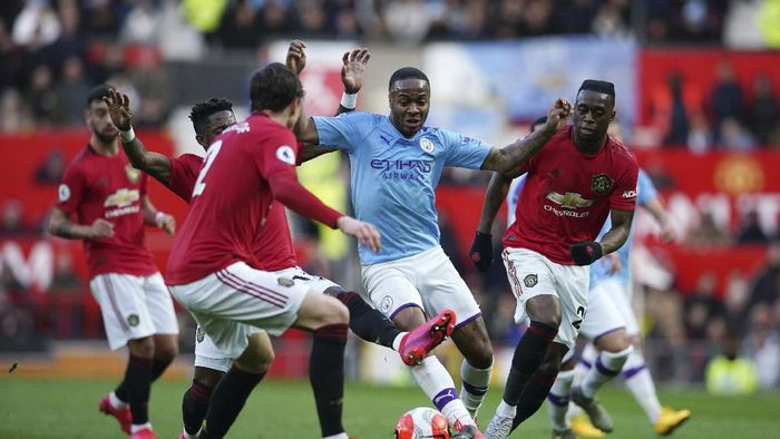 Manchester Citys Raheem Sterling, center, fights for the ball during the English Premier League soccer match between Manchester United and Manchester City at Old Trafford in Manchester, England, Sunday, March 8, 2020. (AP Photo/Dave Thompson)