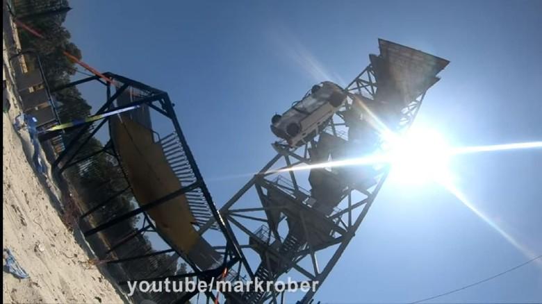 Sebuah mobil dijatuhkan dari ketinggian 45 meter dan disambut oleh sebuah trampolin