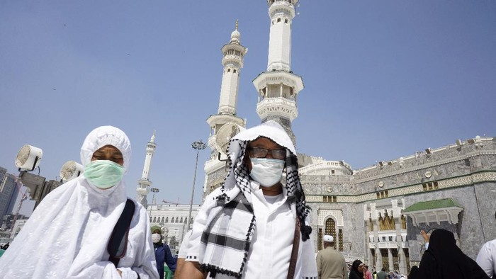 Muslim worshippers wear masks after the noon prayers outside the Grand Mosque, in the Muslim holy city of Mecca, Saudi Arabia, Saturday, March 7, 2020. Few worshippers were allowed to circumambulate the Kaaba, the cubic building at the Grand Mosque, over fears of the new coronavirus. (AP Photo/Amr Nabil)