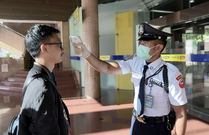 Petugas Keamanan PT Bank Tabungan Negara (Persero) Tbk. mengukur suhu para karyawan dan pengunjung yang akan masuk ke dalam lingkungan kerja perseroan, di Jakarta, Selasa (10/3). Begini potretnya.