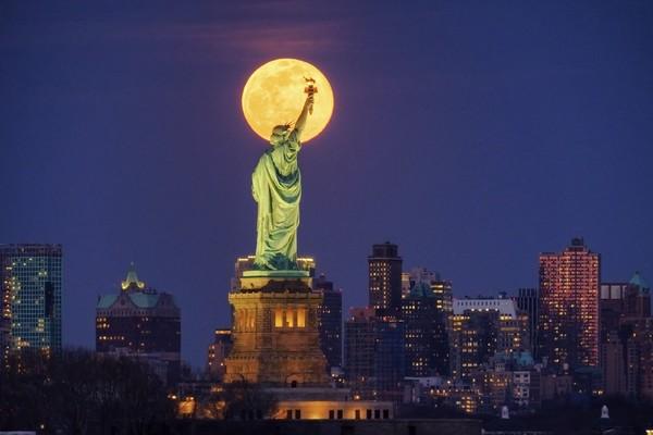 Begini penampakan supermoon yang terlihat di New York, Amerika Serikat. Tepatnya berada di atas Patung Liberty.