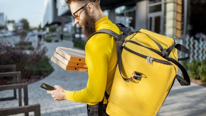Young male courier in yellow sweatshirt delivering pizza, standing with thermal backpack and smart phone on the steret outdoors