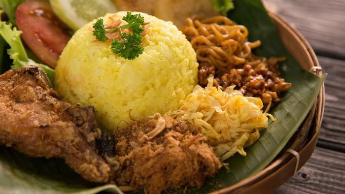 nasi kuning. indonesian yellow rice served with fried chicken on banana leaf