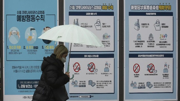 A woman wearing a face mask passes by posters about precautions against the COVID-19 illness on a street in Seoul, South Korea, Tuesday, March 10, 2020. For most people, the new coronavirus causes only mild or moderate symptoms, such as fever and cough. For some, especially older adults and people with existing health problems, it can cause more severe illness, including pneumonia. The sign reads
