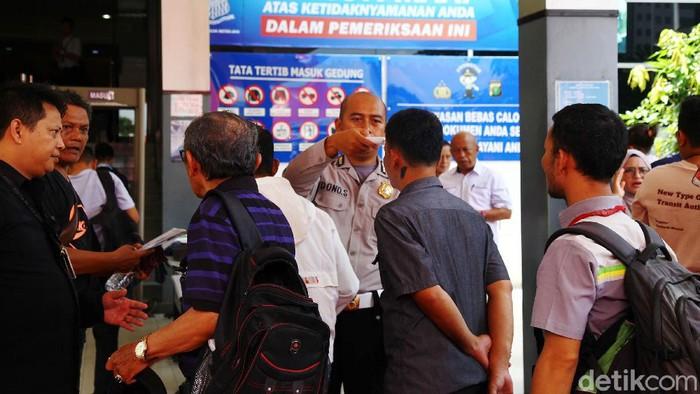 Seorang petugas dari kepolisian Polda Metro Jaya melakukan pemeriksaan pengunjung yang akan ke loket pelayanan publik, Samsat Jakarta Selatan dan Sentra Pelayanan Kepolisian Terpadu (SPKT) di Polda Metro Jaya, Jakarta Selatan, Selasa (10/3/2020). Pemeriksaan tersebut untuk mencegah penyebaran virus Corona.