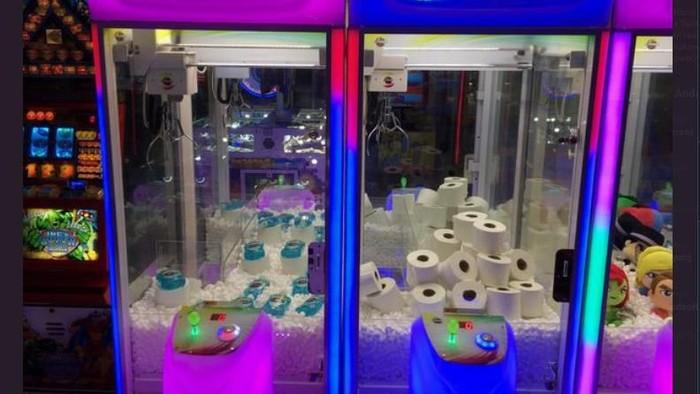 mesin permainan yang berisi tisu toilet dan hand sanitizer.