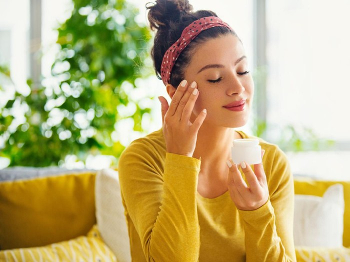 Young woman with eyes closed applying face cream.
