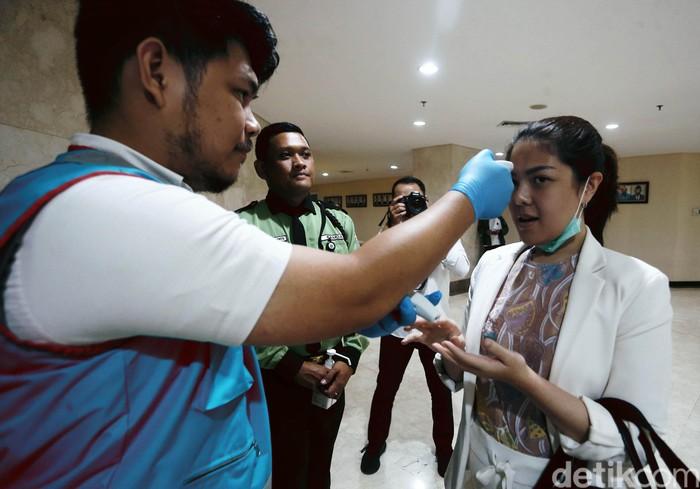 Tina Toon bersama anggota DPRD DKI Jakarta lainnya dicek suhu tubuhnya sebelum rapat paripurna, Rabu (11/3/2020). Pemeriksaan suhu tubuh anggota DPR DKI Jakarta itu menggunakan thermal gun.