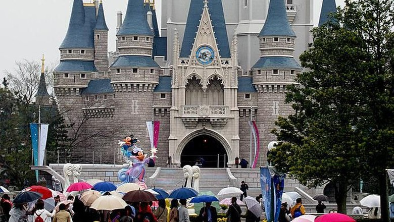 URAYASA, JAPAN - APRIL 15:  People walk in front of the Cinderella Castle at the 20th Anniversary of Tokyo Disneyland April 15, 2003 in Urayasu, Japan.  (Photo by Junko Kimura/Getty Images)