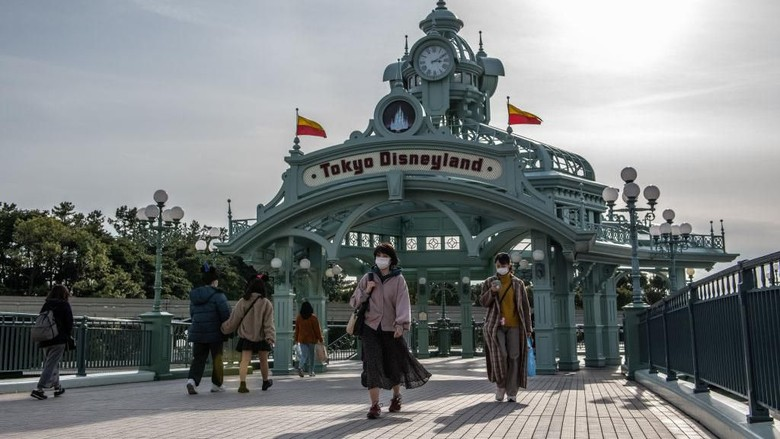 TOKYO, JAPAN - FEBRUARY 28: People pass beneath an archway leading to Tokyo Disneyland on the day it announced it will close until March 15th because of concerns over the Covid-19 virus, on February 28, 2020 in Tokyo, Japan. A growing number of events and sporting fixtures are being cancelled or postponed around Japan while some businesses are closing or asking their employees or work from home. Prime Minister Abe has also asked schools to close for around a month as Covid-19 cases continue to increase and concerns mount over the possibility that the outbreak will force the postponement or even cancellation of the Tokyo Olympics. (Photo by Carl Court/Getty Images)
