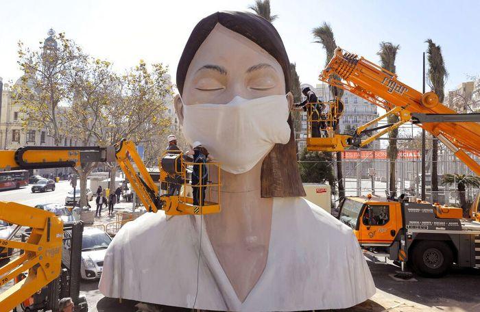 Sejumlah pekerja memasang masker di salah satu patung raksasa yang akan ditampilkan di festival Las Fallas, Valencia, Spanyol, Rabu (11/3/2020) waktu setempat.
